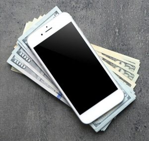 iphone on top of a pile of money